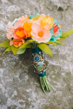 paper flower bouquet with colorful wrap, photo by Carina Skrobecki http://ruffledblog.com/seattle-art-gallery-wedding #weddingbouquet #bouquetwrap #paperflowers