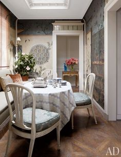 In the dining room, George III chairs surround a table set with a tablecloth of Jasper silk and Oka dinnerware.