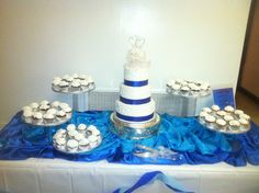 Royal blue and white 3 tier presentation cake with cascading stands of cupcakes.
