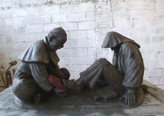 Pope Francis putting the red papal shoes on a homeless person. Symbolic sculpture of what is happening daily with the Pope. - Timothy P. Schmalz