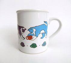Coffee mug featuring colorful cats playing with balls of yarn.