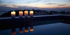 the village of Oia by candelight IKIES Hotel Oia, Santorini, Greece Santorini Hotels, Greece Hotels, Santorini Greece, Beautiful Candles, Candle Set, Marina Bay Sands, Warm And Cozy, Bucket, Wanderlust
