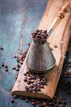 Roasted coffee beans in a cooper turk on a vintage background, copy space