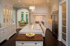 Great millwork, especially the arch into the sunroom beyond. Dark floors and grey blue walls ground the space a little (and no see-thru subzero - cute in magazines, but in real life no one wants to see your milk/ketchup/leftovers etc - and no red knobs). Butcher block at the end of the island is both useful and adds contrast to the expanse of milky marble.  (Source: allthekingshouses)