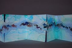 Riverrun III by Julie Wagner. One-of-a-kind accordion book.  Ink, watercolor and hand-carved rubber stamps on suminagashi paper.  H. 5″  W. 6″  48″ open.