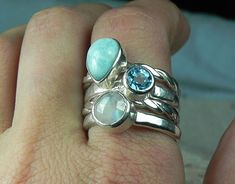 Stacking rings with larimar, rainbow moonstone, and blue topaz in sterling silver are inspired by the colors and patterns of the beautiful caribbean ocean and blue sky. This is a 4 piece stacker ring set, and a chunky one at that. Genuine 7x10mm baby blue, pear shaped larimar,