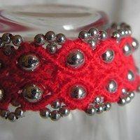 Náramek z červené příze a stříbrných plastových korálků v kovové úpravě. Je široký 22 mm a 19 cm vč. zapínání na kovový knoflík s červenou ozdobou.