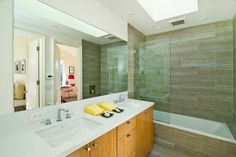 A Jack and Jill bathroom includes dual vanities and skylights. Photo: Robert Vente Photography