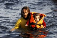 A volunteer lifeguard carries a baby as a half-sunken catamaran carrying around 150 refugees, most of them Syrians, arrives after crossing part of the Aegean sea from Turkey on the Greek island of Lesbos Friday. 2015 (Photo: Giorgos Moutafis/ Reuters).
