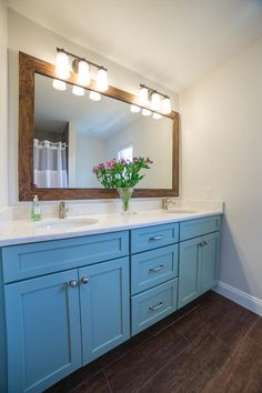 A rustic wood-framed mirror and wood-look tile floors pair with soft, neutral walls and striking sea blue cabinets for a coastal look in this double vanity bathroom. Crisp white quartz countertops complete the beautiful design.