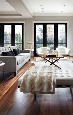 Modern urban-style living room. Clean, minimalist furniture with a sleek silhouette. The cowhide rug adds character, while the neutral colors and dark-grain wooden floors offer a very sophisticated and gender-neutral aesthetic.