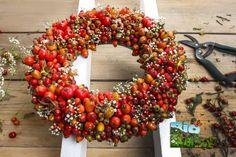 Recolecta ramitas y frutos que caigan de los árboles y átalos en una hermosa corona decorativa.