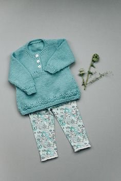 Girls turquoise tunic sweater with simple lace and button detailing at neck. Find this baby pattern and more knitting inspiration at LoveKnitting.Com.