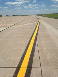 A taxi line is a line that directs pilots to and from a runway. They are always yellow. This is a taxi line. Following this line guarantees that the pilots wing will clear any obstruction that it overhangs.