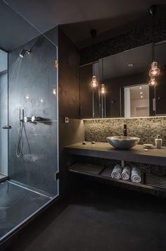 Lavabo escuro,em cinza e marrom com espelho retroiluminada e bulbos pendentes