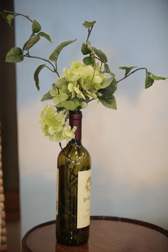 Lighted table decoration made from a wine bottle, lights and artificial flower stems.