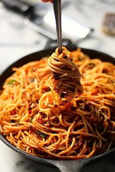 Simple Spaghetti Fra Diavolo: 2/3 cup olive oil  10 cloves garlic, sliced very thin or minced  1 1/2 teaspoons crushed red pepper flakes (add a little more if you really like the spice!)  2 1/2 cups tomato puree  1/2 cup fresh basil leaves, thinly sliced  1/4 cup fresh mint leaves, roughly chopped  1/4 cup fresh parsley, roughly chopped  2 teaspoons salt  1/2 teaspoon black pepper  1 pound of spaghetti, cooked al dente #simple