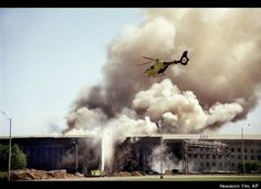 A helicopter flies over the Pentagon in Washington, Tuesday, Sept. 11, 2001 as smoke billows over the building. The Pentagon took a direct, devastating hit from an aircraft and the enduring symbols of American power were evacuated.