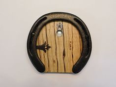This unique fantasy door is made from solid wood with a recycled horseshoe frame. It features a metal door handle, metal hinges and a glass