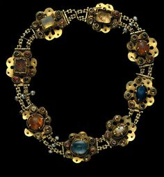 Colar de ouro da Rainha Stª Isabel, Século XIV (1ª metade).Portugal. Rare gold necklace, enriched by the contrasting colours of the precious stones, belonged to the bequest of the Queen, Saint Isabel. It consists of 8 multi-lobed plates, linked by two parallel chains and accented by 9 baroque pearls in groups of 3. The central gems (3 sapphires, 1 glass, 1 glass doublet and 2 topazes) are surrounded by a collar, encircled on the base with a typical medieval setting of small beads.
