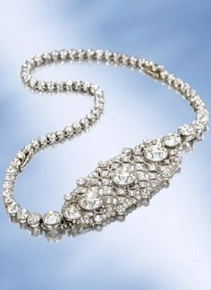 AN ELEGANT BELLE EPOQUE DIAMOND CHOKER  Designed as an articulated diamond openwork oval panel, the centre set with three circular-cut diamonds, to the graduated diamond collet necklace, detaching to form two bracelets or a brooch and a bracelet, circa 1905, necklace 36.0 cm long, bracelets 18.5 and 17.5 cm long