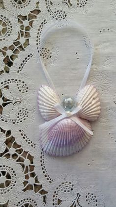 """28 - Seashell Angel ornament.  This handmade seashell Angel ornament measures 2 1/4"""" x 2 1/2"""" x 1/2"""" and was painted with Mother of Pearl, Purple Martin and Sugar Cube.  A white bow and ribbon complete this lilac angel."""