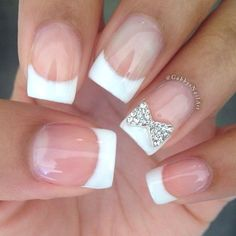 French tips with a silver rhinestone bow nail design
