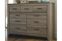 Urban sophistication with a decidedly relaxed air. If effortless elegance is the impression you're going for, the Zelen dresser is custom made to fit your space. It's got the crisp, clean lines of a contemporary piece, but with softly weathered elements, including antiqued industrial pulls and an earthy finish that lets the beauty of replicated oak grain flow through. Seven smooth-gliding drawers of varied size make it a bedroom essential.
