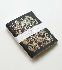 Pocket notebook features metallic gold foil floral design.