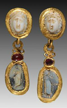 PAIR OF OPENWORK ROMAN GOLD EAR PENDANTS WITH CAMEOS of a facing female on the upper section of each and suspending a gold pendant with cameos of Eros figures; adorned with garnets. Ca. 3rd Century AD.