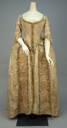 Robe à la francaise, France, 1774-1793. Cream silk open robe having silver metallic stripe and polychrome silk floral brocade, elbow length sleeve trimmed in knotted net with silk ribbon and tambour embroidered floral applique, neckline, bodice and skirt trimmed in metallic lace and ribbon flowers, self buttons on bodice back for tying up skirt, skirt having front panels appliqued with horizontal bands of net, lace and floral embroidery decorated with red, blue and silver foil, sacque back…