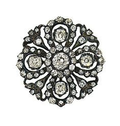 A late 19th century diamond brooch  The circular openwork brooch centrally-set with an old brilliant-cut diamond cluster, within a diamond-set surround of foliate design, mounted in silver and gold, circa 1890, pin deficient, 3.5cm wide