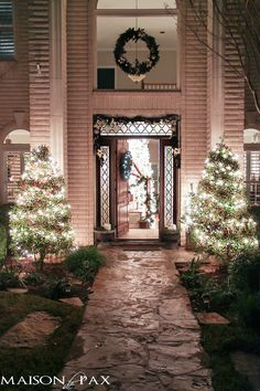 holiday front porch with garland, wreath, and lights