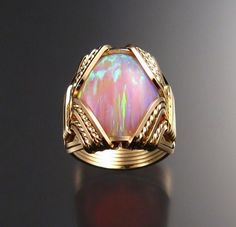 Pink opal ring. The design it's just arrestingly beautiful but the opal is ... Starts with a C... A real opal that big would cost nothing less than 3000$. I really love opals, and I bought a tiny Australian one and it cost double of this.   Why don't they just call it pink stone ring?
