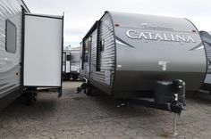 """UNIQUE REAR KITCHEN MAKES COOKING EASY!  2017 Coachmen Catalina Legacy Edition 283RKS For spacious, comfortable living in the great outdoors, this 32' 6"""" Catalina is it! With a dry weight of just 6,509 lbs., it offers a surprising amount of Limited Edition amenities: 32"""" TV, 15' power patio awning with lights, SS range with oven, outdoor shower, solar power prep, bath skylight, and more! Give our Catalina Legacy Edition expert Karin Florida a call 810-834-9851 for pricing and more information. Coachmen Rv, Rv Dealers, Deck Railings, Rvs For Sale, Skylight, Solar Power, The Great Outdoors, Recreational Vehicles, Michigan"""