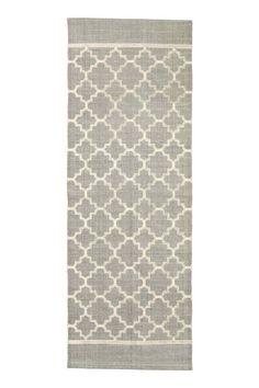 Bawełniany chodnik we wzory: Podłużny chodnik z bawełnianej tkaniny we wzorzyste nadruki na wierzchu.