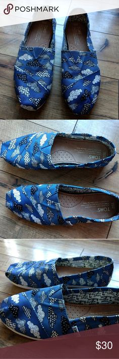 TOMS Blue Sky clouds slip on loafer shoes New without tags TOMS slip on shoes. These were a store return. They are in new condition but have writing on the Soles.  Singing in the Rain blue with black and white clouds. Toms Shoes Flats & Loafers