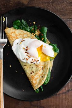 Homemade cornmeal crepes stuffed with garlicky sautéed spinach and topped with a poached egg- perfect for breakfast or a light lunch.