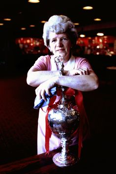 May Devine, a cleaner in the Anfield trophy room polishes the First Division league championship trophy before placing it back in the cabinet. Exact date unknown. Photo: Steve Hale.