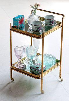 Xícaras, vasos, taças e vasinho com flores decoram este carrinho de chá de ferro, que fica lindo em vários cantos da casa.