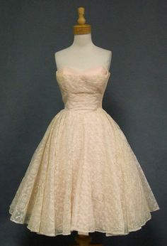 A feminine 1950's cocktail dress in a light creamy pink nylon with pink and cream floral embroidery.