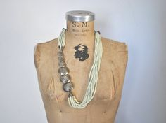 This is a great 1970's necklace made of large hammered metal beads and thousands of tiny mint color beads. I love the asymmetrical design. Very