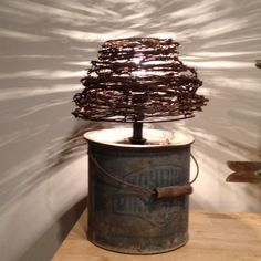 lamp made from old metal container and wrapped barbed wire