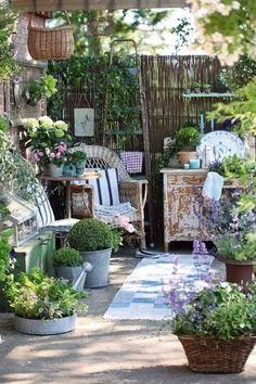brise-vue en branchettes, mobilier en bois rustique et plantes sur la terrasse