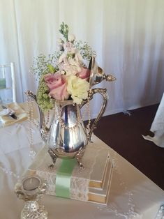 Delicate Elegance Events - Vintage wedding. Antique silver coffee / tea pot centerpieces on books covered with lace & ribbon