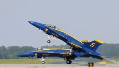 While Blue Angel number 5, Lieutenant Commander Ben Walborn, in the foreground already is airborne, Blue Angel number 6, Lieutenant C.J. Simonsen, in the background, still is making speed with all wheels on the runway.  Shot taken during an Airshow at  MCAS Beaufort, South Carolina, May this year.