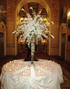 Tall white orchid centerpiece with elegant candle lighting.