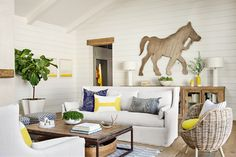 This living room has tons of country style from steep-pitched ceiling, paneled walls painted with Benjamin Moore's White Dove, wood floors, and an influx of natural light.