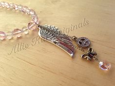 Beaded necklace with metal feather charm