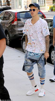 Relaxed: The pop star added ripped overalls, which he wore unbuttoned...